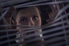 Портрет красивой загадочной женщины смотря через jalousie, жалюзи Стоковая Фотография RF