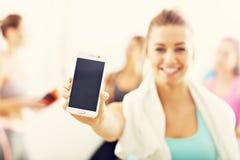 Портрет красивой зрелой женщины с smartphone усмехаясь в оздоровительном клубе стоковое фото rf