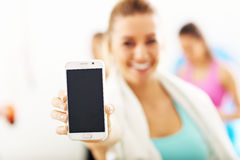Портрет красивой зрелой женщины с smartphone усмехаясь в оздоровительном клубе стоковые фото