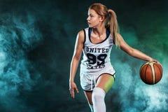 Портрет красивой и сексуальной девушки с баскетболом в студии изолированная принципиальной схемой белизна спорта стоковые фотографии rf