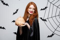 Портрет красивой кавказской ведьмы держа тыкву для праздновать хеллоуин стоковое фото