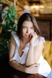 Портрет красивой кавказской коммерсантки сидя на таблице на кресле Стоковые Фото