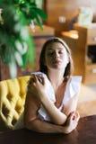Портрет красивой кавказской коммерсантки сидя на таблице на кресле Стоковая Фотография RF