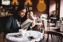 Портрет красивой книги чтения девушки в кафе питье Стоковое Фото
