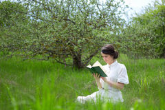 Портрет красивой книги чтения женщины на луге лета Стоковые Изображения RF