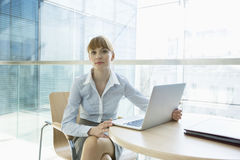 Портрет красивой коммерсантки при компьтер-книжка сидя на таблице в офисе Стоковые Изображения RF
