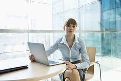 Портрет красивой коммерсантки при компьтер-книжка сидя на таблице в офисе Стоковые Фотографии RF