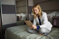 Портрет красивой коммерсантки сидя на кровати и используя таблетку Стоковые Изображения RF