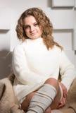 Портрет красивой курчавой женщины в свитере и шерстях socks sitt Стоковые Изображения