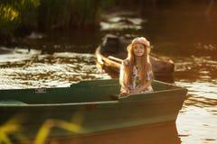 Портрет красивой маленькой девочки в шлюпке на заходе солнца на озере Стоковое Фото