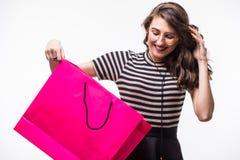 Портрет красивой милой счастливой удивленной помадкой девушки женщины держа в ее хозяйственной сумке рук большой изолированной на Стоковые Фото