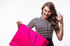 Портрет красивой милой счастливой удивленной помадкой девушки женщины держа в ее хозяйственной сумке рук большой изолированной на Стоковые Изображения
