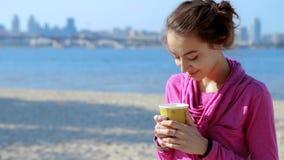 Портрет красивой молодой атлетической женщины в кофе розового hoodei sportswear выпивая от бумажного стаканчика на песке города видеоматериал