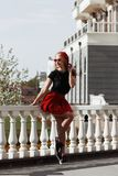 Портрет красивой молодой белокурой женщины нося стильное черное обмундирование, она усмехаясь на городской предпосылке стоковое изображение
