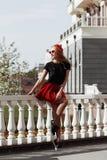 Портрет красивой молодой белокурой женщины нося стильное черное обмундирование, она усмехаясь на городской предпосылке стоковое фото