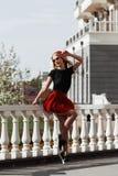 Портрет красивой молодой белокурой женщины нося стильное черное обмундирование, она усмехаясь на городской предпосылке стоковая фотография