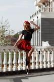 Портрет красивой молодой белокурой женщины нося стильное черное обмундирование, она усмехаясь на городской предпосылке стоковые фото