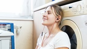 Портрет красивой молодой домохозяйки при наушники полагаясь на стиральной машине на прачечной стоковая фотография