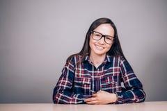 Портрет красивой молодой женщины брюнет с стеклами на таблице Бизнес-леди девушки смотря с улыбкой на камере Стоковые Изображения
