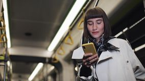 Портрет красивой молодой женщины в наушниках ехать публично переход, слушает музыка и просматривающ на желтом цвете сток-видео