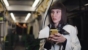 Портрет красивой молодой женщины в наушниках ехать публично переход, слушает музыка и просматривающ на желтом цвете видеоматериал