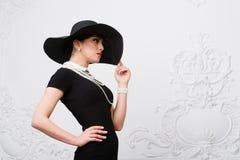 Портрет красивой молодой женщины в ретро стиле в элегантных черной шляпе и платье над роскошной предпосылкой стены рококо Стоковая Фотография RF