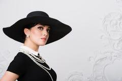 Портрет красивой молодой женщины в ретро стиле в элегантных черной шляпе и платье над роскошной предпосылкой стены рококо Стоковые Изображения RF