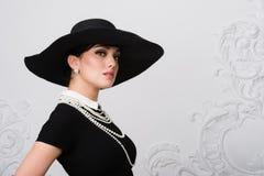 Портрет красивой молодой женщины в ретро стиле в элегантных черной шляпе и платье над роскошной предпосылкой стены рококо Стоковые Фотографии RF