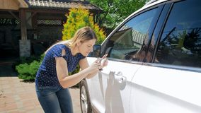 Портрет красивой молодой женщины делая фотоснимки из ее автомобиля после аварии Стоковое Изображение