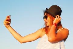 Портрет красивой молодой женщины делая selfie на умном телефоне Стоковые Фотографии RF