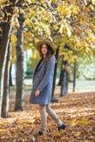 Портрет красивой молодой женщины идя outdoors в парк осени в уютных пальто и шляпе Теплая солнечная погода Концепция падения стоковые фотографии rf