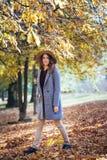 Портрет красивой молодой женщины идя outdoors в парк осени в уютных пальто и шляпе Теплая солнечная погода Концепция падения стоковые изображения