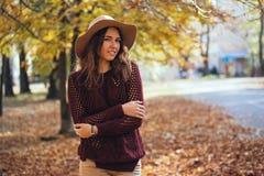 Портрет красивой молодой женщины идя outdoors в парк осени в уютных свитере и шляпе Теплая солнечная погода падение стоковые фотографии rf
