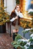 Портрет красивой молодой женщины которая представляет на улице около элегантно украшенного окна рождества, праздничное настроение стоковое изображение rf