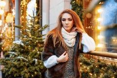 Портрет красивой молодой женщины которая представляет на улице около элегантно украшенного окна рождества, праздничное настроение стоковое фото