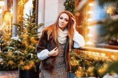 Портрет красивой молодой женщины которая представляет на улице около элегантно украшенного окна рождества, праздничное настроение стоковые изображения