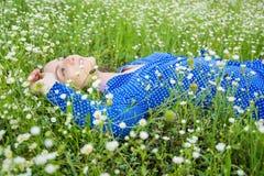 Портрет красивой молодой женщины лежит среди белых wildflowers Стоковые Фото