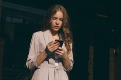 Портрет красивой молодой женщины с длинными волосами и розовыми ногтями держа ее телефон в снаружи лета стоковые фотографии rf