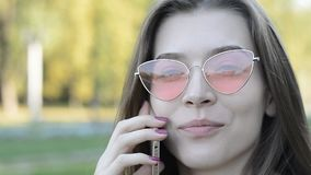 Портрет красивой молодой кавказской женщины в розовых солнечных очках которая говорит на телефоне в парке видеоматериал