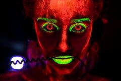 Портрет красивой молодой сексуальной девушки в наушниках с ультрафиолетов краской на ее теле Милая женщина с накалять стоковое изображение rf