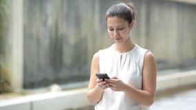 Портрет красивой молодой счастливой женщины Outdoors используя мобильный телефон акции видеоматериалы