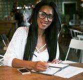 Портрет красивой молодой чернокожей женщины сидя на кафе и исковом заявлении Стоковое Изображение