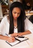 Портрет красивой молодой чернокожей женщины сидя на кафе и исковом заявлении Стоковое Изображение RF