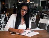 Портрет красивой молодой чернокожей женщины сидя на кафе и исковом заявлении Стоковые Фотографии RF