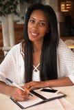 Портрет красивой молодой чернокожей женщины сидя на кафе и исковом заявлении Стоковая Фотография