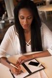 Портрет красивой молодой чернокожей женщины сидя на кафе и исковом заявлении Стоковая Фотография RF