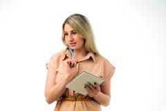 Портрет красивой молодой белокурой женщины думая с блокнотом, изолированной белой предпосылки Стоковое Изображение RF