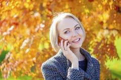 Портрет красивой молодой женщины вызывая телефоном Стоковые Изображения