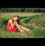 Портрет красивой молодой женщины в красном платье на предпосылке неба и травы в лете Стоковые Фото