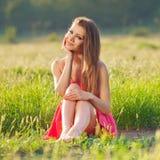 Портрет красивой молодой женщины в красном платье на предпосылке неба и травы в лете Стоковое Фото